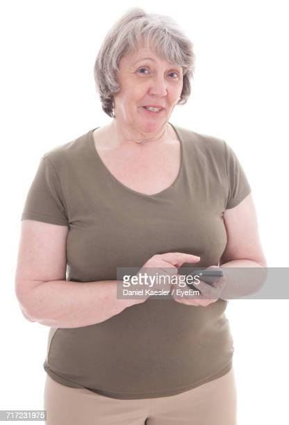 Portrait Of Senior Woman Using Phone Against White Background