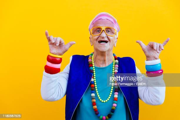 portrait of senior woman wearing colorful jewelry standing against yellow background - multi colored hat stock pictures, royalty-free photos & images
