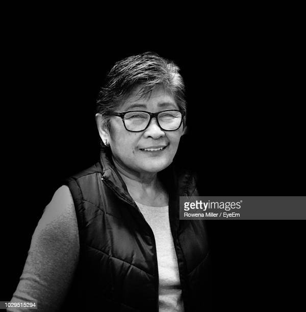 portrait of senior woman wearing eyeglasses against black background - rowena miller stock photos and pictures