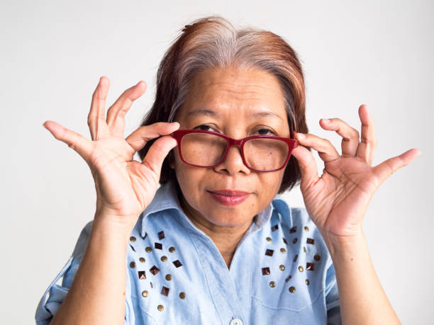 portrait of senior woman wearing eyeglasses against white background - serious and old asian woman with eye glasses stock pictures, royalty-free photos & images