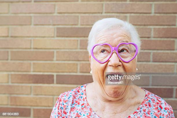 portrait of senior woman wearing heart-shaped glasses pulling funny faces - mischief stock photos and pictures