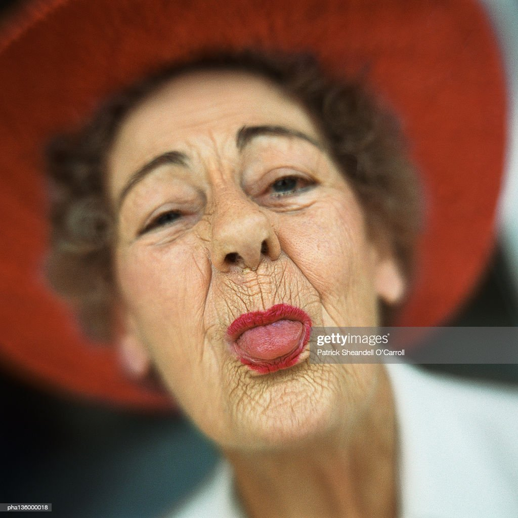 Portrait of senior woman wearing red hat with tongue sticking out : Stockfoto