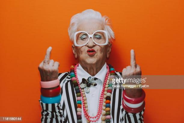 portrait of senior woman wearing showing obscene gesture against red background - old lady middle finger stock pictures, royalty-free photos & images