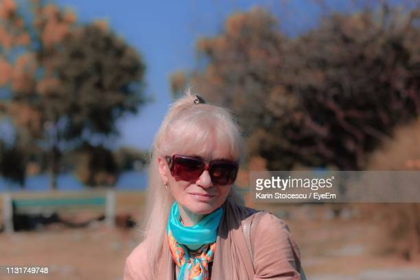 Portrait Of Senior Woman Wearing Sunglasses In Park During Sunny Day