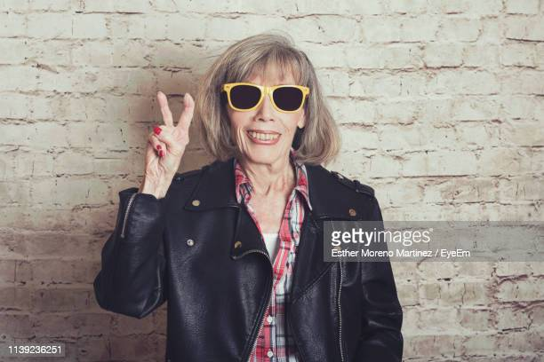 portrait of senior woman wearing sunglasses while gesturing peace sign against brick wall - レザージャケット ストックフォトと画像