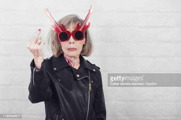 portrait of senior woman wearing sunglasses while showing obscene gesture against wall - old lady middle finger stock pictures, royalty-free photos & images
