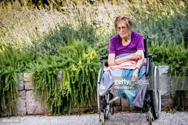 portrait of senior woman mit amputeted beinen sitzen im freien am rollstuhl - amputee woman stock-fotos und bilder
