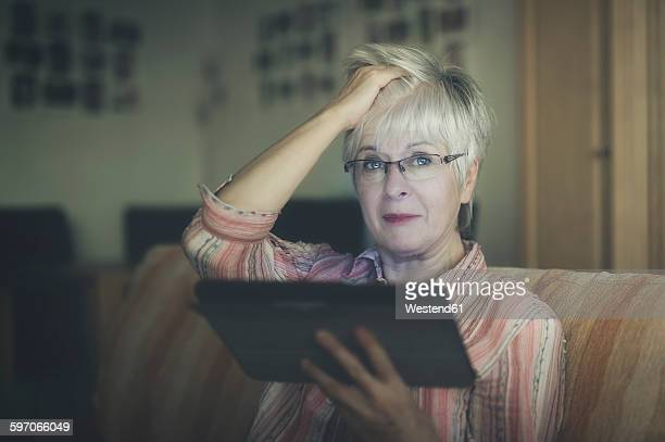 portrait of senior woman with digital tablet - desaturated stock pictures, royalty-free photos & images