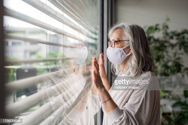 portrait of senior woman with face mask standing indoors by window at home, looking out. - long stock pictures, royalty-free photos & images