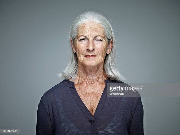 Portrait of senior woman with grey hair in front of grey background