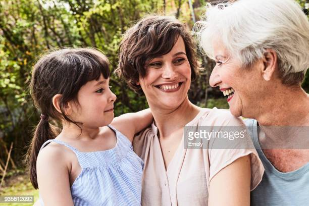 portrait of senior woman with grown daughter and granddaughter, outdoors, smiling - generational family stock photos and pictures