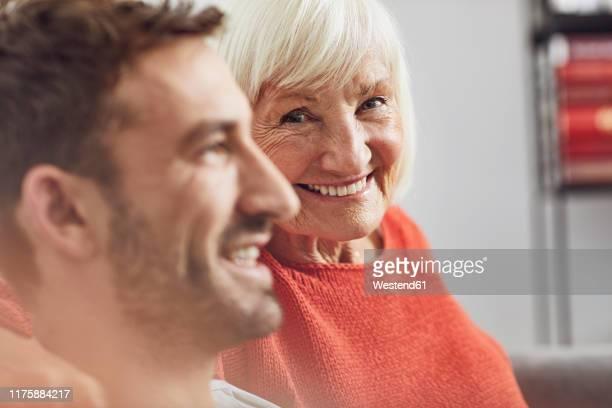 portrait of senior woman with her grown-up grandson - nur erwachsene stock-fotos und bilder