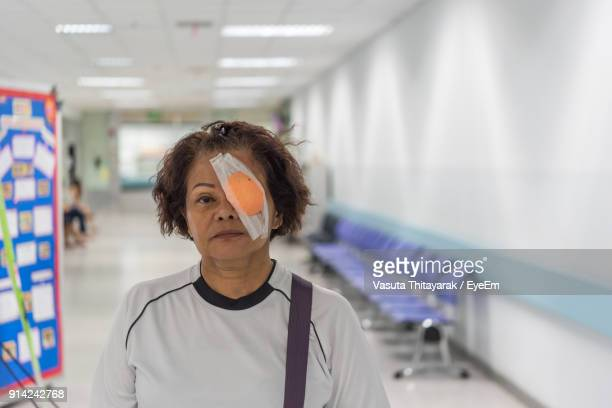 Portrait Of Senior Woman With Medical Eye Patch Standing At Hospital