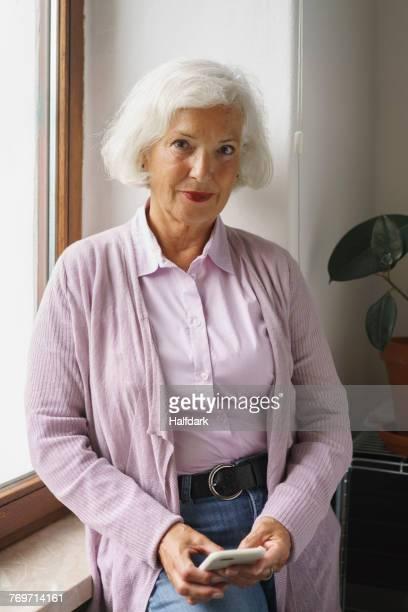 portrait of senior woman with mobile phone leaning on window sill at office - eine seniorin allein stock-fotos und bilder