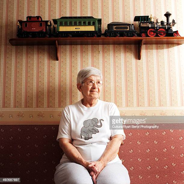 Portrait of senior woman with train set on shelf