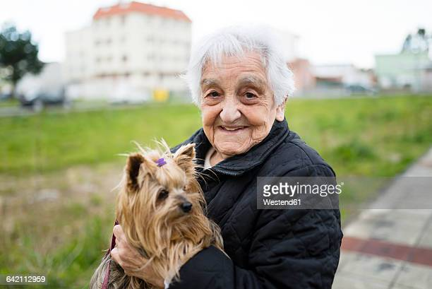 Portrait of senior woman with Yorkshire Terrier on her arms