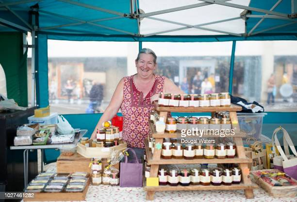 portrait of senior woman working on local market stall. - market stall stock pictures, royalty-free photos & images