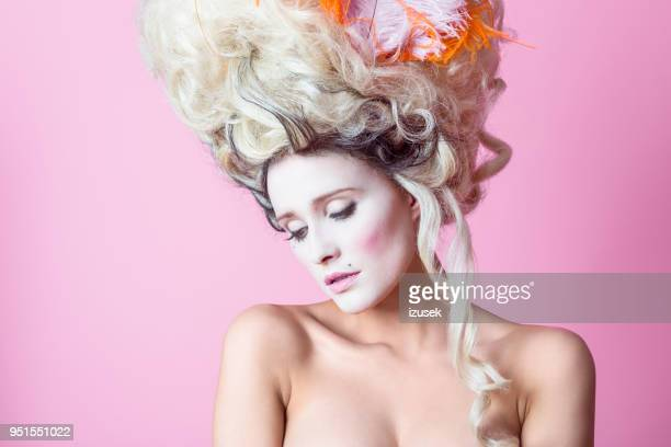 Portrait of sensual baroque woman wearing wig, pink backgroud