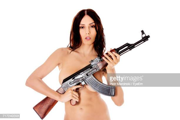 Portrait Of Sensuous Naked Woman Holding Ak-47 Against White Background