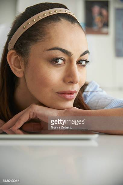 Portrait of sensuous woman leaning on table at home