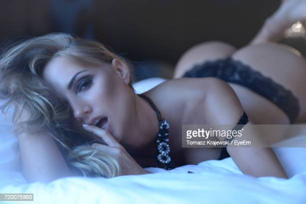 portrait of sensuous woman lying down on bed at home - mujeres sensuales fotografías e imágenes de stock