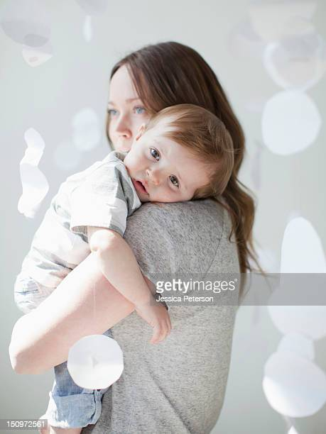 Portrait of serene young woman embracing baby boy (6-11 months)