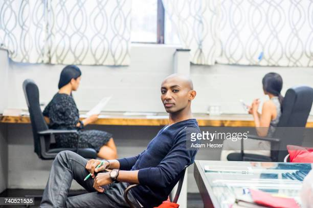 portrait of serious african american man sitting in office - black transgender stock pictures, royalty-free photos & images