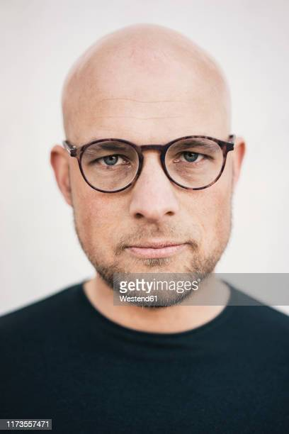 portrait of serious bald man with beard wearing glasses - haarausfall stock-fotos und bilder