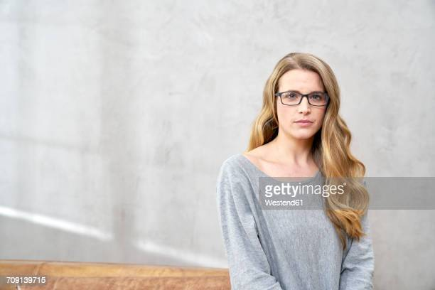 Portrait of serious blond woman wearing glases