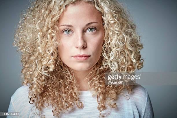 portrait of serious blond woman with curly hair - gelockt stock-fotos und bilder