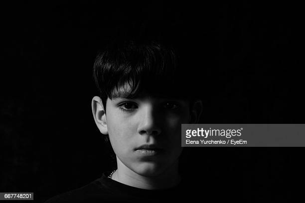 Portrait Of Serious Boy Against Black Background