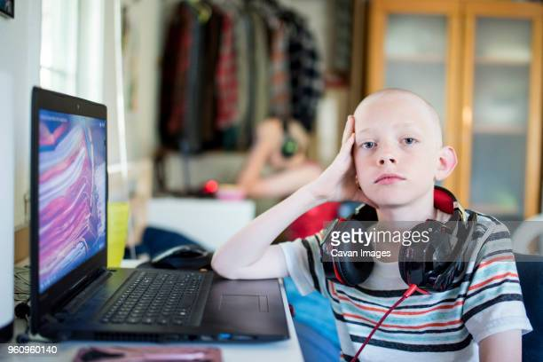 Portrait of serious boy with headphones at home
