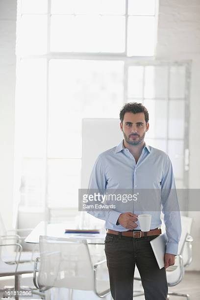 Portrait of serious businessman holding coffee cup and digital tablet in office
