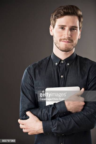 Portrait of serious businessman holding digital tablet