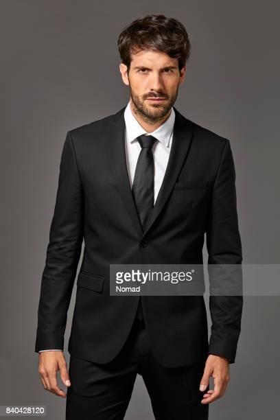Portrait of serious businessman in black suit
