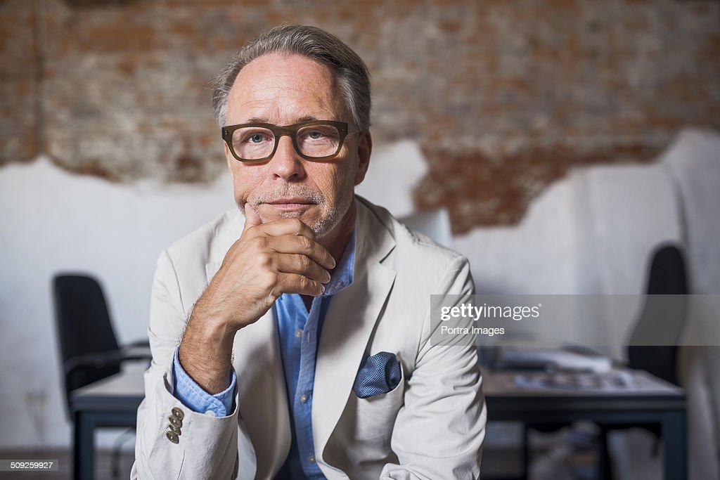 Portrait of serious businessman in creative office : Stock Photo