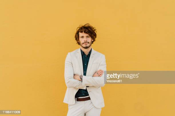 portrait of serious businessman in front of yellow wall - assertiveness stock pictures, royalty-free photos & images