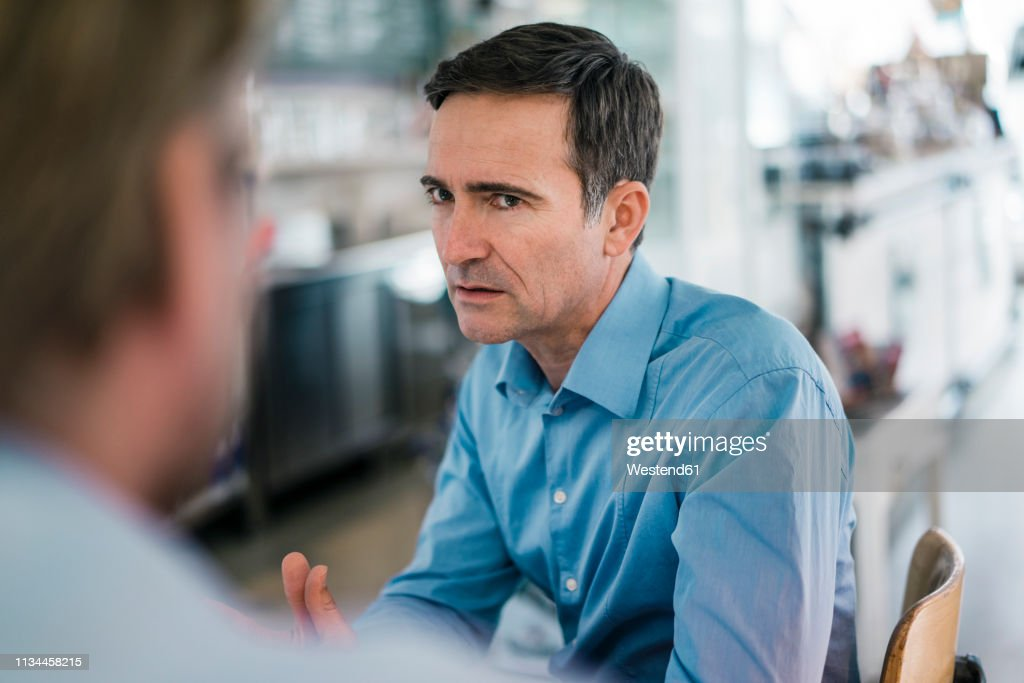 Portrait of serious businessman looking at colleague : Stock Photo