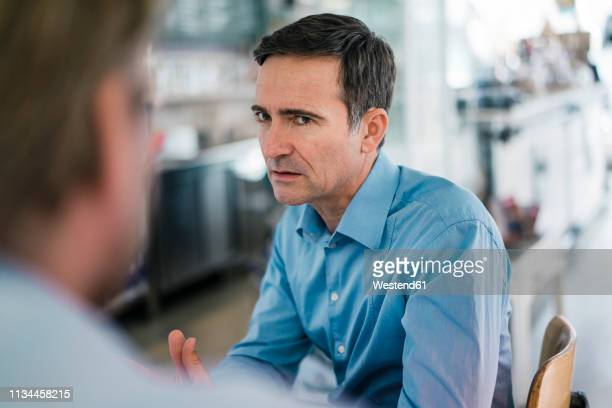portrait of serious businessman looking at colleague - anger stock pictures, royalty-free photos & images