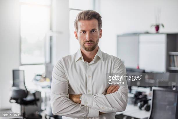 portrait of serious businessman with arms crossed in the office - da cintura para cima imagens e fotografias de stock
