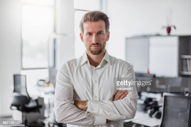 portrait of serious businessman with arms crossed in the office - encuadre cintura para arriba fotografías e imágenes de stock