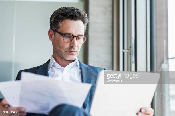 Portrait of serious businessman with documents looking at tablet
