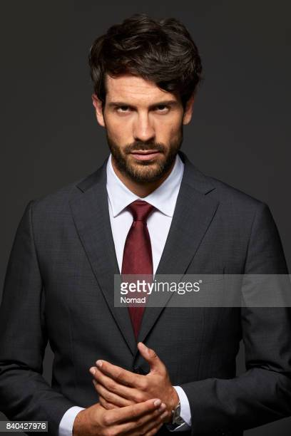 Portrait of serious businessman with hands clasped