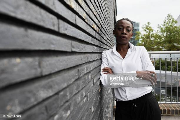 Portrait of serious businesswoman leaning against wall