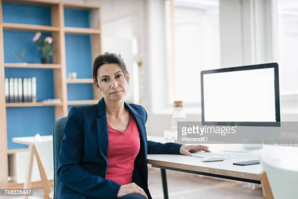 Portrait of serious businesswoman sitting at desk in a loft