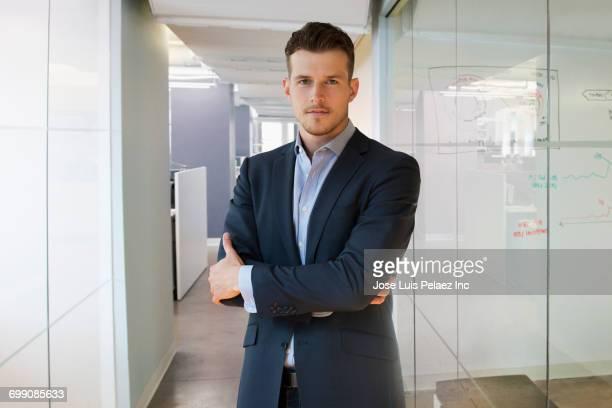 portrait of serious caucasian businessman standing in office corridor - braços cruzados - fotografias e filmes do acervo