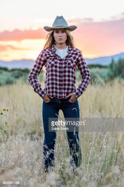Portrait of serious Caucasian teenage girl wearing cowboy hat at sunset