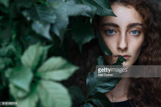 portrait of serious caucasian woman behind leaves - environmentalist stock pictures, royalty-free photos & images