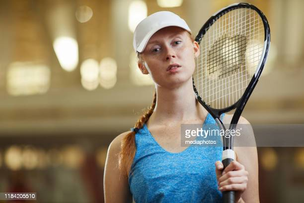 portrait of serious confident young redhead lady in white cap standing on court and holding tennis racquet - tennis player stock pictures, royalty-free photos & images