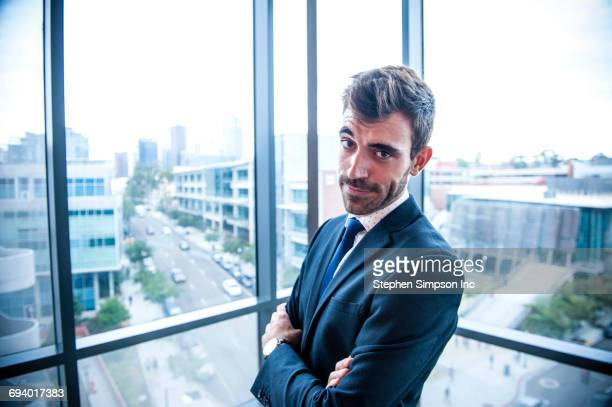 Portrait of serious Hispanic businessman posing near window